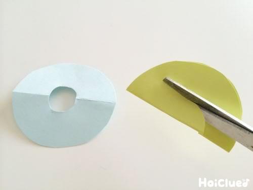 半分に折った丸い画用紙の真ん中をハサミでくり抜く様子