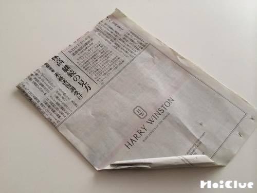 新聞紙を角からくるくる細長く丸めている写真