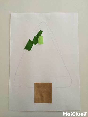 ちぎった折り紙を木の形に貼っていく写真