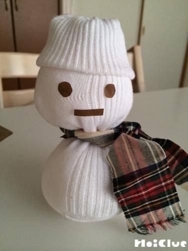 折り紙で作った顔を貼り、首にマフラーを巻いた雪だるまの写真