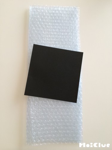 気泡緩衝材と黒い折り紙の写真
