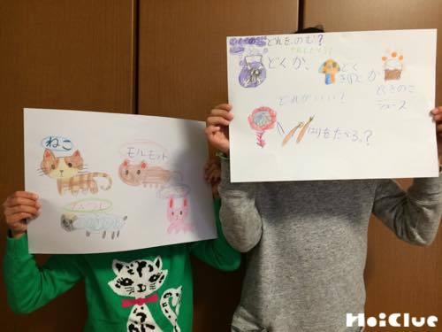 絵を描いた画用紙を掲げる子どもの写真