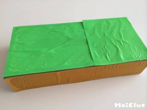 ティッシュ箱の底に緑の折り紙を貼った写真