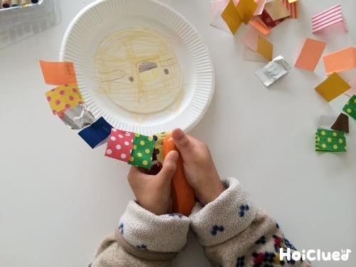 紙皿の周りに長方形に切った折り紙をホッチキスでとめる様子