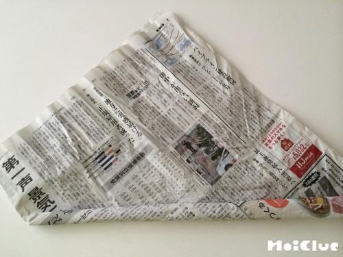 新聞紙を端から丸めている写真