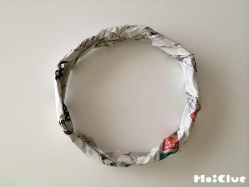 細く丸めた新聞紙で輪っかを作った写真