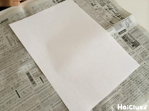 新聞紙の上に白紙をおいた写真
