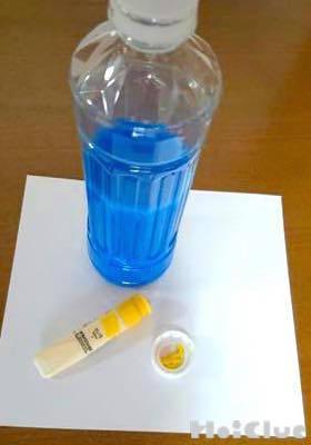 青い絵の具で色を付けた水を入れたペットボトルと、内側に黄色い絵の具をつけたペットボトルキャップ