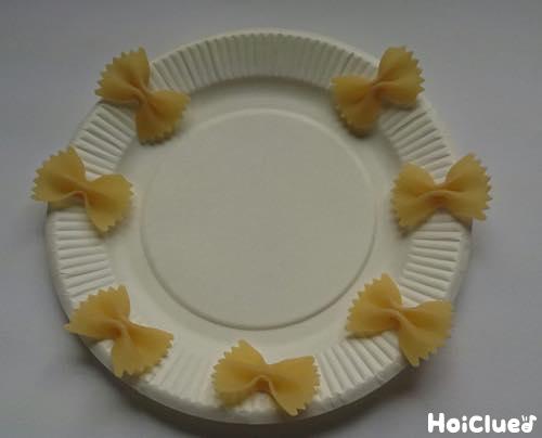 紙皿にちょうちょの形のパスタ(ファルファッレ)をくっつけた写真