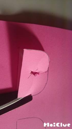 画用紙から鱗の形を切り抜いている写真