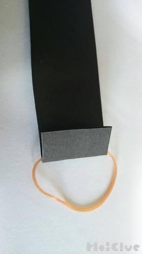 細長い折り紙に輪ゴムをつけた写真