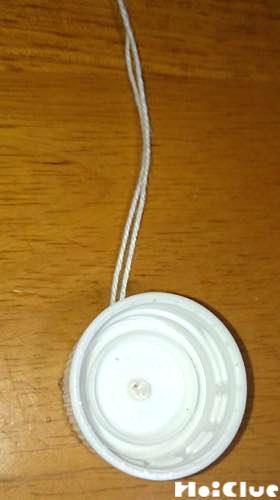 穴を開けたペットボトルキャップにタコ糸を通した写真