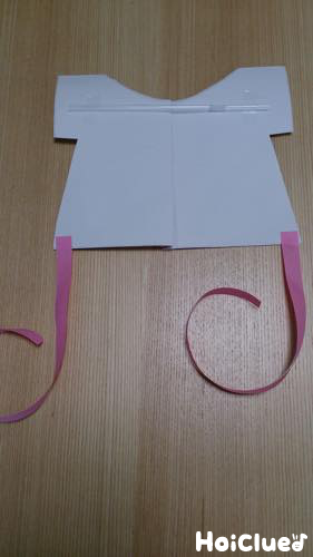 裏側の袖部分に横にストローを、裾の両端に紙テープを貼った写真