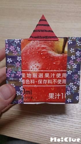 切り取った牛乳パックに紙を貼り付けている写真