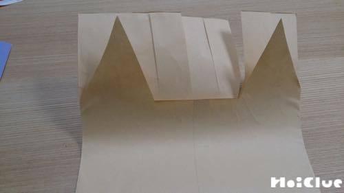 封筒の上部に縦に切り込みを入れた一枚と上部をツノの形に切り取った一枚の写真