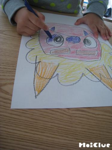 画用紙に鬼の顔を描いている写真