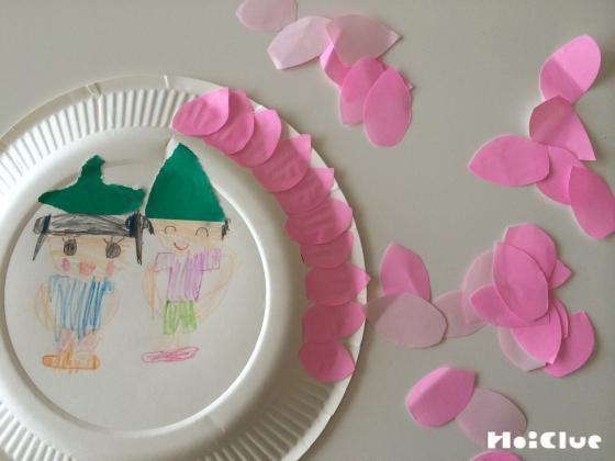 紙皿のふちにピンクの花びらの形に切った折り紙を貼り付けている写真