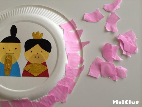 紙皿のふちにピンク色のちぎった折り紙を貼り付けている写真