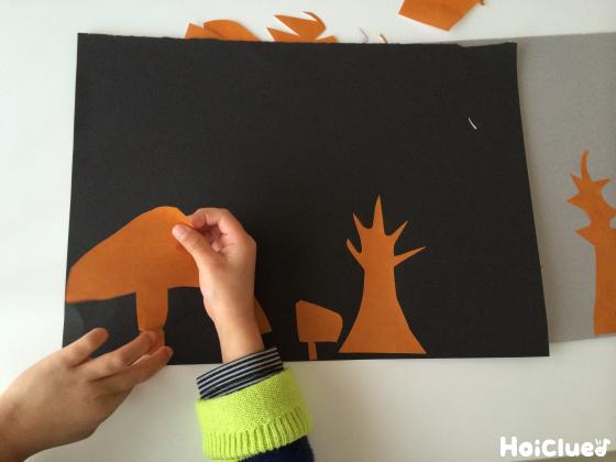 黒い画用紙の上に茶色い画用紙で家や木の形を作って載せいている写真
