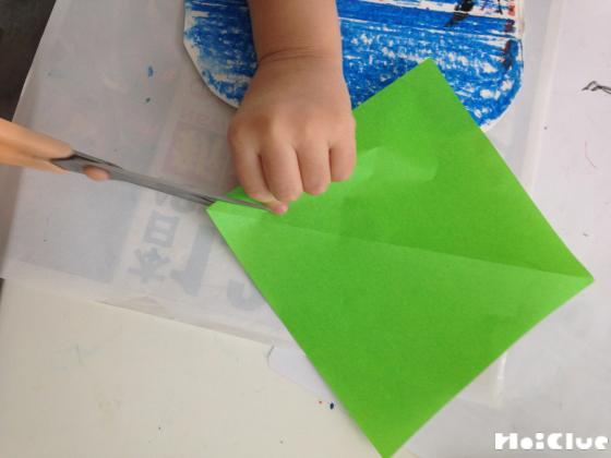 折り紙を折って切っている写真