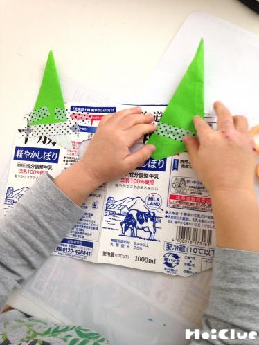 牛乳パックの顔に切った折り紙を貼り付けている写真