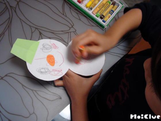 切り取った厚紙に雪だるまの絵を描いている写真