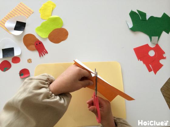 画用紙をハサミで切り色々なおかずを作る子どもの様子