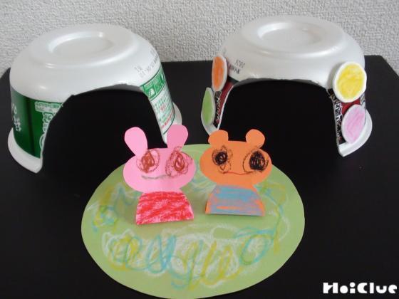 かまくらの入り口を切り抜いたカップ麺の容器と、丸い画用紙に固定した動物の写真