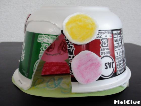 丸い画用紙の上に固定したカップ麺の容器に2個目の容器を重ねた様子