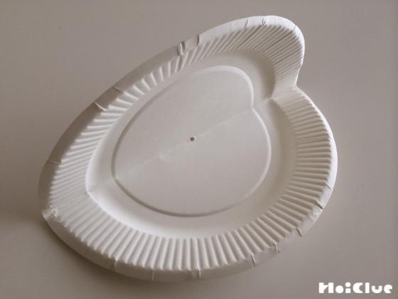紙皿を半分に折り中心にきりで穴を開けた写真