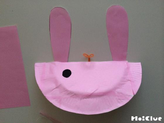 全体にピンクの折り紙を貼り耳を付けうさぎにする様子