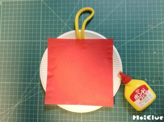 紙皿に赤い折り紙を貼り付けた写真