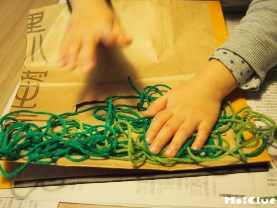 紙袋に毛糸を貼り付けている写真