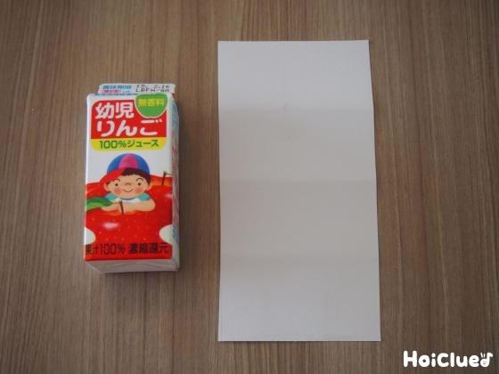ジュースの紙パックと白い画用紙の写真