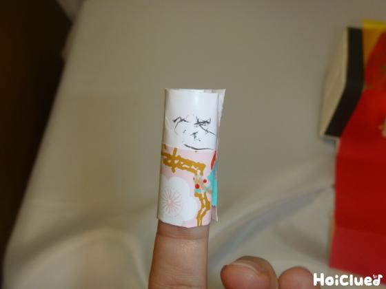 人差し指に紙を巻いている写真