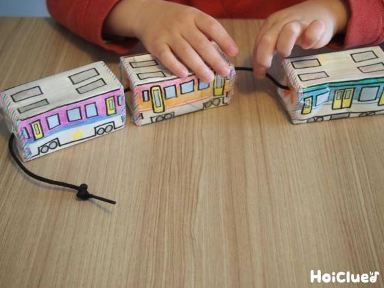 3個の電車を紐でつなぎ合わせる子どもの様子