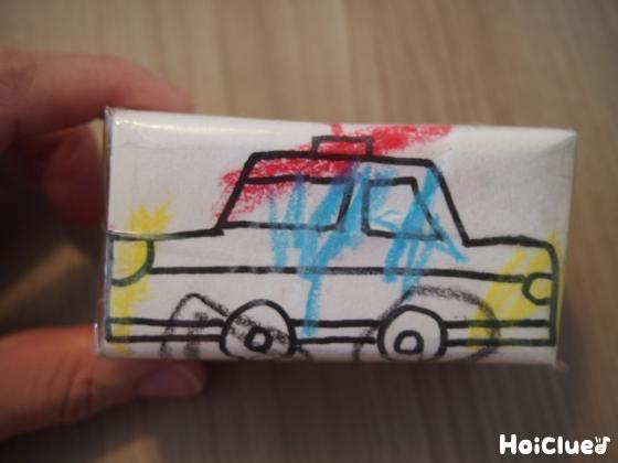 紙パックに貼った画用紙に電車の絵を描いた写真