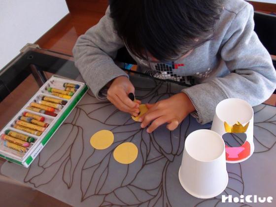 丸い画用紙に絵を描く子どもの様子