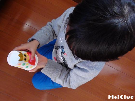 重ねた紙コップを回して遊ぶ子どもの様子