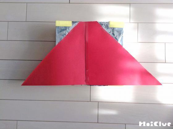 赤い三角形の画用紙をアルミホイルに取り付けている写真