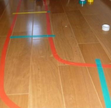 床にビニールテープを貼って線路を作っている写真