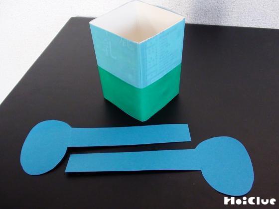 半分に切り下半分部分に画用紙を貼った牛乳パックと、象の耳のパーツ