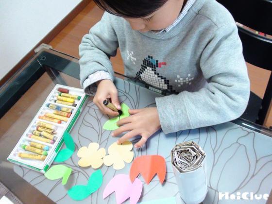 画用紙で作った花や葉に絵を描く子どもの様子