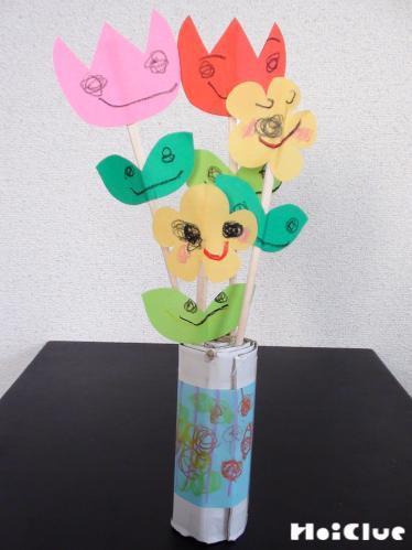 段ボールに割り箸の花をさし完成した花瓶の写真