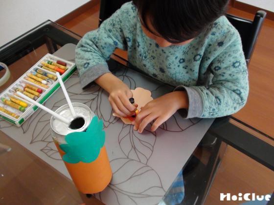 缶の側面に木を貼り、フクロウに絵を描く子どもの様子