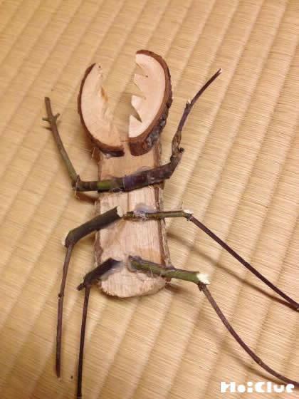 胴体の裏側に細い枝で足を取り付ける様子