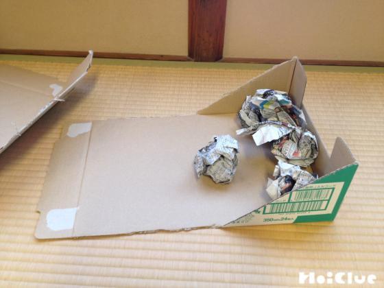土台となる箱の中の部分に丸めた新聞紙を詰め込む様子