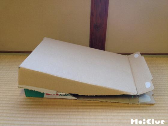 新聞紙を詰めた箱に同じ様に作ったダンボールをフタの様に被せる様子
