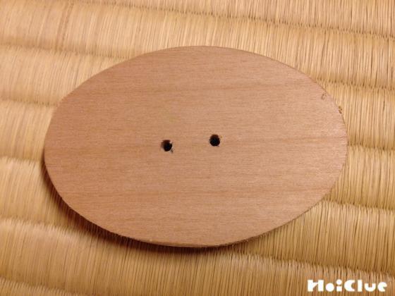真ん中に2ヶ所穴を開けた楕円形の木片