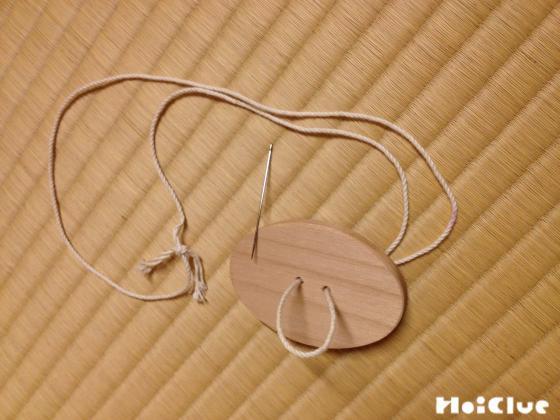 木片の穴にタコ糸を通す様子